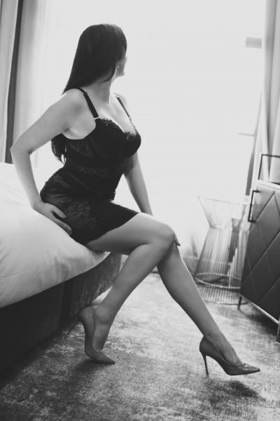 NZ Pleasures Black and white photo of Miss Jordan Quinn perching on the side of a bed, back arched, one leg extended, the other bent back against the bed. One hand is resting on the knee of her extended leg, the other on the side of her hip. Miss Jordan Quinn wears a black lace sleeveless short dress and heels.