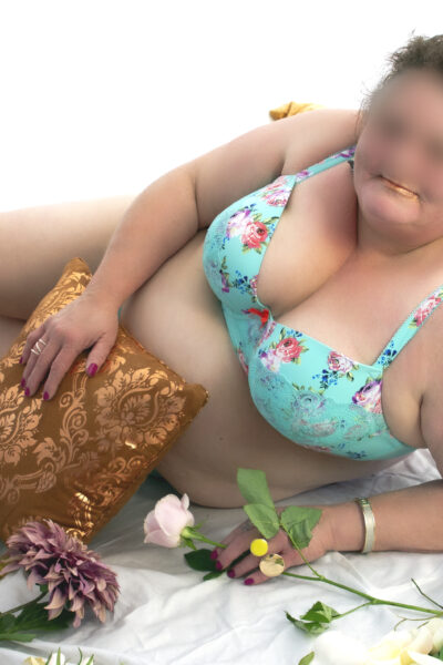 NZ Pleasures. Addison Lane lying on her side, leaning up on elbow, her other hand holding a pillow in front, knees bent up. Addison wears light green floral lingerie and has medium length brown hair.
