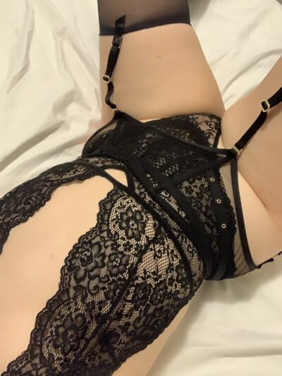 NZ Pleasures. Chloe Beaumont lying on her back, legs apart. Chloe wears a black lace bodysuit with suspender belt and stockings.