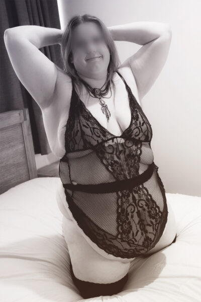 NZ Pleasures Black and white photo of Vanessa kneeling on a bed, knees apart, hands up behind head, smiling at the camera. Vanessa wears a lace bodysuit and thigh high stockings.