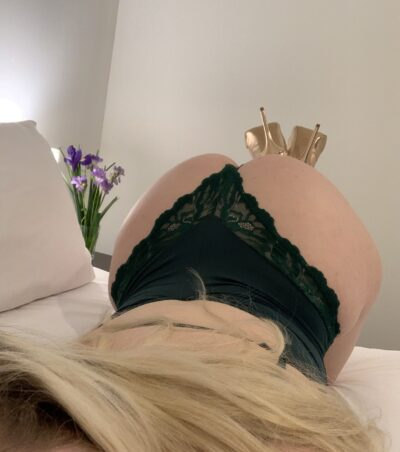 NZ Pleasures. Over the shoulder photo of Chloe Beaumont kneeling on the bed, chest on bed, legs in air, crossed at ankles. Chloe Beaumont wears a black bodysuit with gold heels and has long blonde hair.