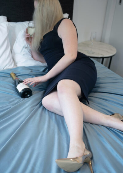 NZ Pleasures. Chloe Beaumont lying on her side on a bed of blue, one leg bent under the other, holding a glass of wine. Chloe Beaumont wears a sleeveless dress with gold heels and has long blonde hair.