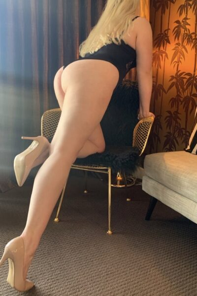 NZ Pleasures. Chloe Beaumont kneeling on one knee on a chair, the other leg extend out behind her, hands on top of chair. Chloe Beaumont wears a black bodysuit and beige heels and has long blonde hair.