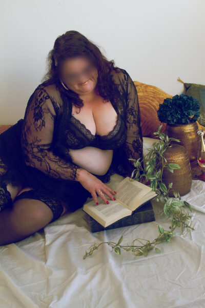 NZ Pleasures. Addison Lane sitting reading a book, leaning on one hand, the other resting in the book, knees bent up. Addison Lane wears black lingerie and has medium length brown hair.