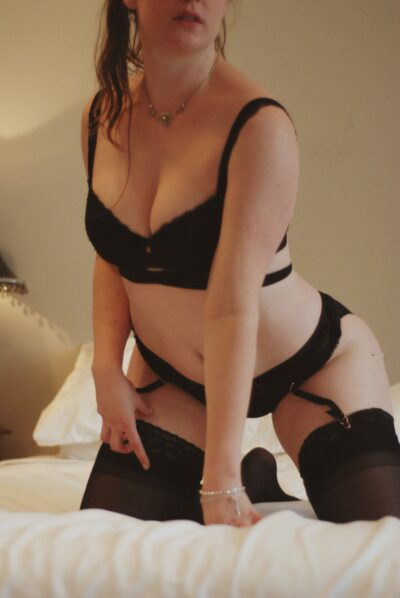 NZ Pleasures Amelia Appleby kneeling on a bed of white, leaning forward on one hand in front of her, her other hand on thigh. Amelia wears black lingerie with suspender and stockings and has long dark hair.