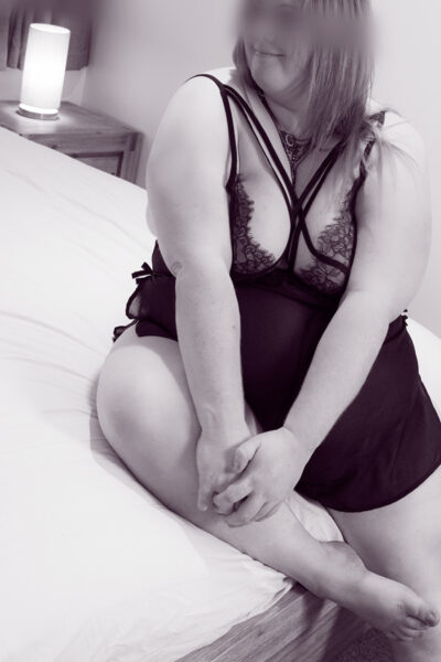NZ Pleasures Black and white photo of Vanessa sitting on the end of a bed, one leg bent up on bed, hands resting on that leg, head turned to one side. Vanessa wears a black teddy and has long hair.
