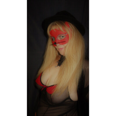 NZ Pleasures. Mary Jane Honey posing with a red cat mask, standing side on to camera. Mary Jane wears a red bra and has long blonde hair.