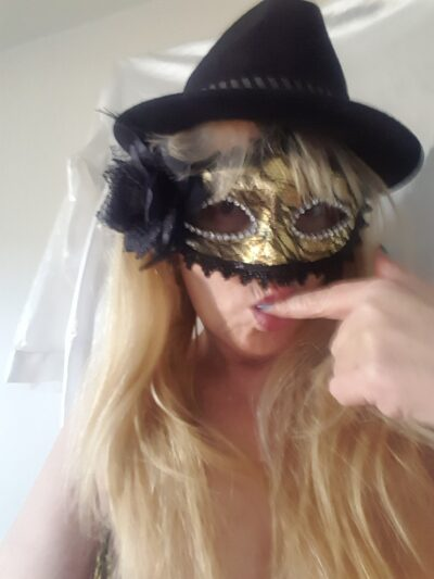 NZ Pleasures. Portrait style photo of Mary Jane Honey wearing a mask and black hat, sucking one finger. Mary Jane has long blonde hair.