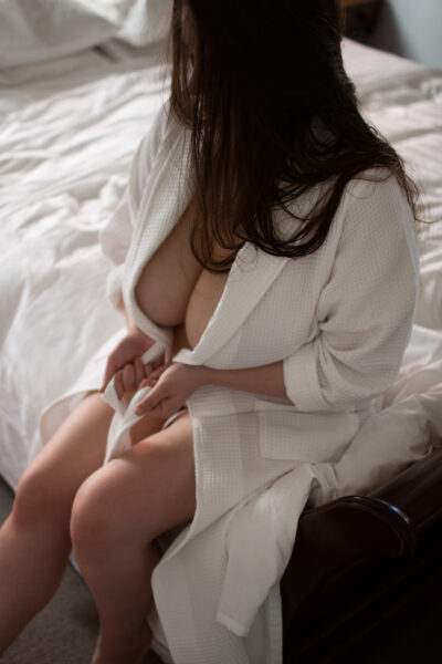 NZ Pleasures. Ashley Monroe sitting on the end of a bed of white, wearing a white robe, cleavage revealed. Ashley Monroe has long brown hair.