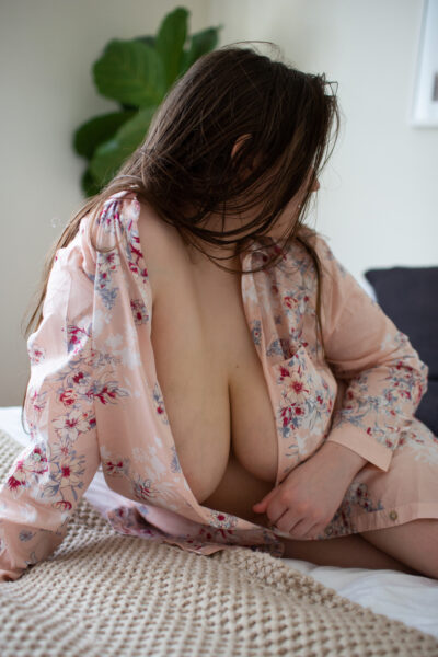 NZ Pleasures. Ashley Monroe leaning on her side on a bed, pushing up from one hand, the other resting below breast, head turned away from camera. Ashley Monroe wears a floral pink kimono that is undone.