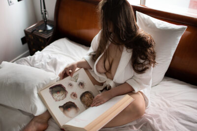 NZ Pleasures. Ashley Monroe sitting on a bed holding a large book in her lap, turned to the page about breast anatomy. Ashley Monroe wears a white robe that is open at the front and has long brown hair.