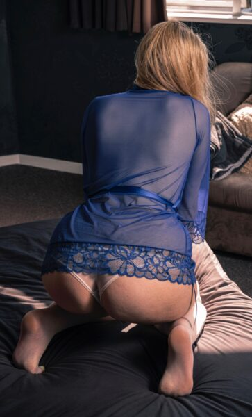 NZ Pleasures. Madison Leigh kneeling with back to camera, hands resting on top of thighs. Madison wears a blue sheer kimono and white panties and has medium length blonde hair.