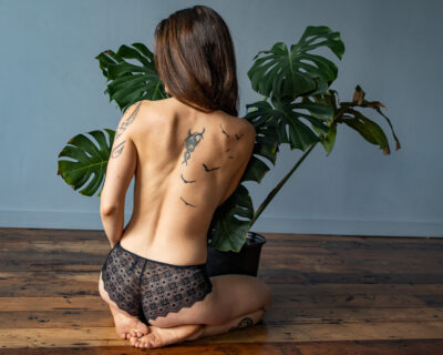 NZ Pleasures Photo taken from behind Ana whose kneeling, sitting back on feet, head turned to one side, a palm plant in front of her. Ana wears black lace panties and has tattoos on her back and arm.