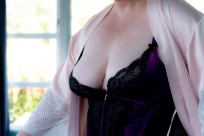 NZ Pleasures Annie posing in a black and purple bodice and pink satin kimono.