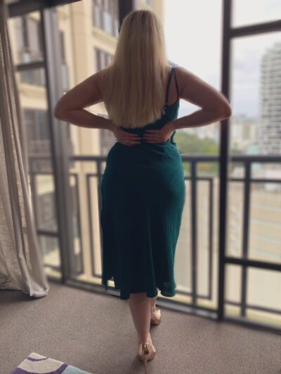 NZ Pleasures. Chloe Beaumont standing at the balcony windows, back to camera, hands on lower back, one foot in front of the other. Chloe Beaumont wears a deep green shoestring strap dress with gold heels and has long blonde hair.