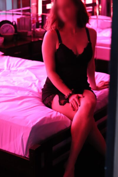 NZ Pleasures. Kali sitting on the end of a bed, legs crossed, one hand beside her, the other resting on side of knee. Kali wears a black teddy and has medium length hair.