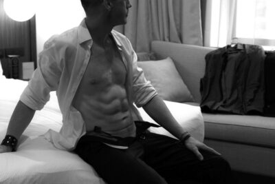 NZ Pleasures Black and white photo of Harley Brixton sitting on the end of a bed, one hand out beside him, the other resting on top of knee, head turned to one side. Harley wears a white shirt and black pants, both of which are undone.