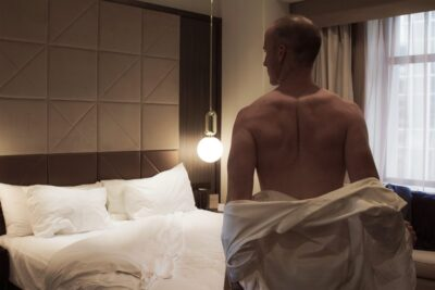 NZ Pleasures Harley Brixton posing with back to camera, his dress shirt half off, standing at the end of a bed.