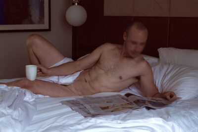 NZ Pleasures Harley Brixton reclining in bed reading a newspaper. One hand holds the paper, the other a cup, which rests on one leg, the other is bent up. Harley is naked, except for the sheet that is draped over his pelvic region.