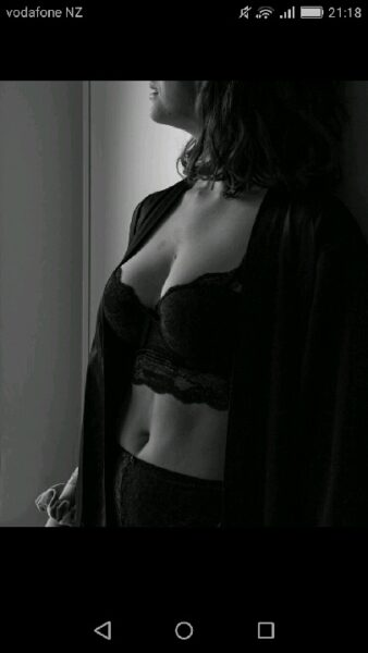NZ Pleasures. Black and white photo of Kalie from chin to hips, head turned away from camera. Kali wears black lingerie.
