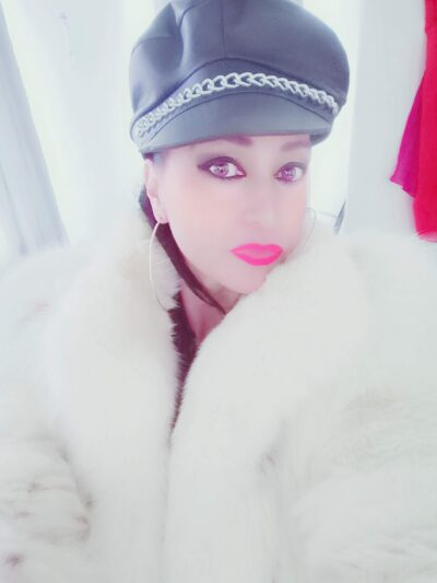 NZ Pleasures Portrait style photo of Mistress Dark Angel wearing a white fur coat and a black leather cap.