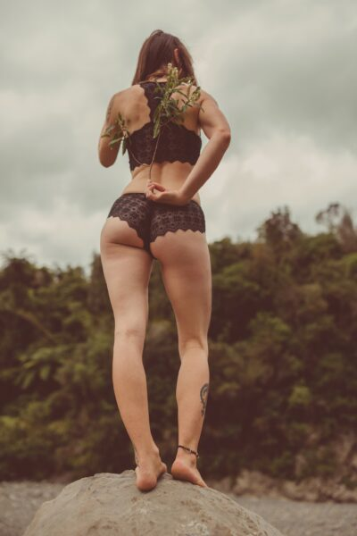 NZ Pleasures Ana standing on a rock in nature, one knee slightly bent, holding a small tree branch behind her back. Ana wears black lingerie and has long hair.