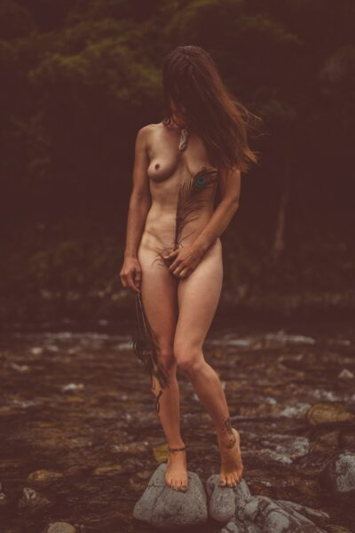 NZ Pleasures Ana standing naked on two stones in a river, hair hiding her face, one hand holding a peacock feather in front of her pelvic region.