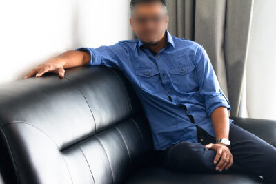 NZ Pleasures. Jon sitting on a couch side on, one knee bent up on couch, one hand on calf muscle, the other across the back of the couch. Jon wears a blue dress shirt and black pants.