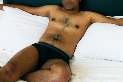 NZ Pleasures. Jon reclining on two pillows on a bed, arms out either side, one knee bent under other leg. Jon wears black jockeys and has chest hair.