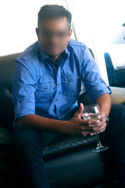 NZ Pleasures. Jon sitting on a couch, legs apart, hands clasped holding a glass of wine, forearms on tops of thighs. Jon wears a blue dress shirt, black pants.