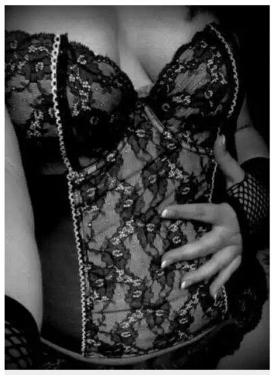 NZ Pleasures Close up black and white photo of Oriana Island Beauty in a lace corset, hand on stomach.