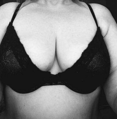 NZ Pleasures Black and white photo of Mary Jane Honey's breasts in a black bra.