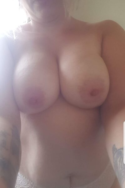 NZ Pleasures Delilah from lips to hips, taking a selfie. Delilah wears white panties and has tattoos on her arms.