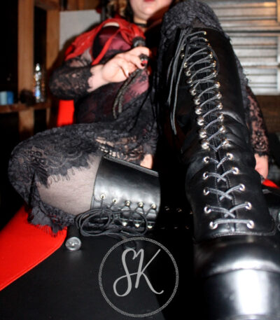NZ Pleasures Close up photo of Sir Kit's knee high black boots, knees bent up.