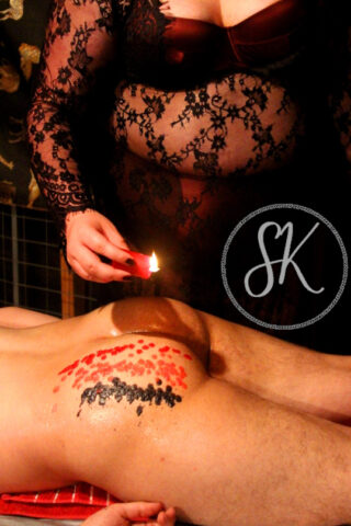 NZ Pleasures Sir Kit dripping body wax onto a clients bare bottom. Sir Kit wears deep burgundy lingerie and black lace dress.