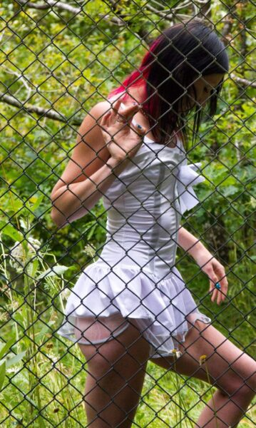 NZ Pleasures Naughty Nikita standing on the other side of a fence, one knee bent up, one hand holding the fence wire. Nikita wears a white corset with mini skirt and has short hair.