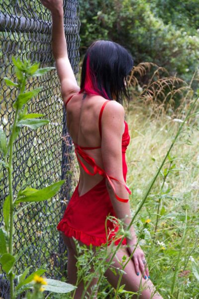 NZ Pleasures Naughty Nikita posing beside a fence, tall grass around her, one hand up on fence, the other on top of thigh. Nikita wears a red teddy.