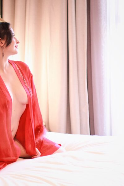 Miss Jordan Quinn kneeling on a bed of white, wearing only a red kimono that is undone, long hair in a ponytail. NZ Pleasures.