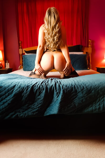 NZ Pleasures. Phoenix kneeling on the middle of a bed, knees wide apart, back to camera, hands on backs of thighs, head titled back. Phoenix wears black lingerie and stockings and has long blonde hair.