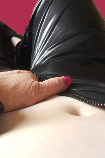NZ Pleasures. Addison lying on her back, knees bent up slightly, one hand in bottom of unzipped black catsuit.