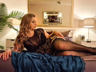 NZ Pleasures. Phoenix lying on her side, leaning up on one elbow, knees bent up, her other hand on top of thigh, head looking at hand. Phoenix wears a black bodysuit with suspender belt and black stockings and has long blonde hair.