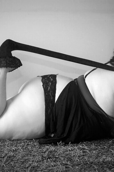 Black and white photo of Vanessa lying on her front, leaning up on elbows, knees bent up, one hand pulling on her stocking which is still on one foot. Vanessa wears a bodysuit and a stiletto on one foot. Vanessa has long brown hair. NZ Pleasures.