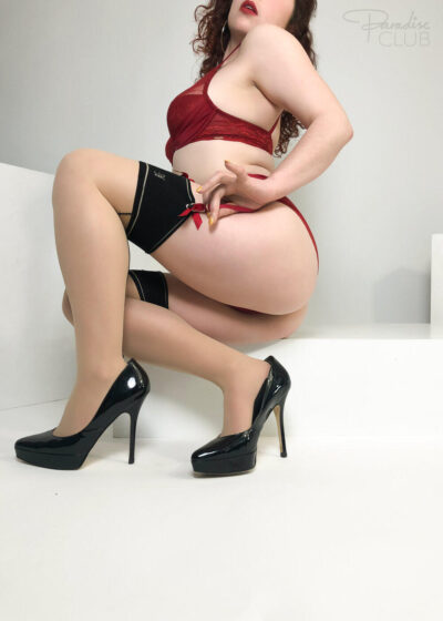 Bianca perching on the end of a step on one buttock, knees bent, one hand tucked into the garter belt strap. Bianca wears deep red lingerie and suspender belt with black topped stockings and black heels and has long dark brown hair. NZ Pleasures.