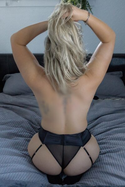 Maddy kneeling on a bed, sitting back on feet, back to camera, hands up in hair. Maddy wears black panties with suspender belt and stockings and has medium length light brown/blonde hair. NZ Pleasures.