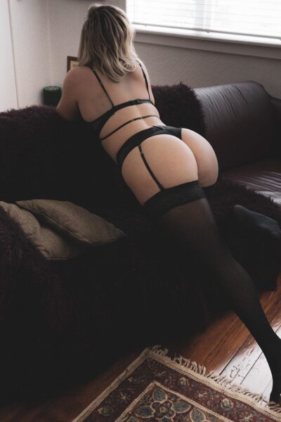 Maddy kneeling on one knee on a couch, leaning over the back of the couch, other leg extended behind her. Maddy wears black lingerie with black stockings and has medium length light brown hair. NZ Pleasures.