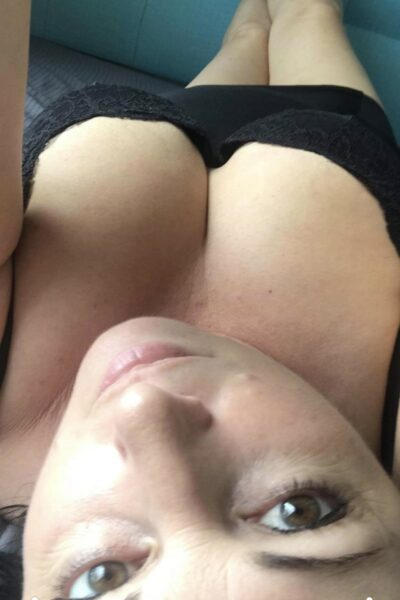Nicky Love taking a selfie from above, looking up at camera. Nicky wears black lingerie. NZ Pleasures.