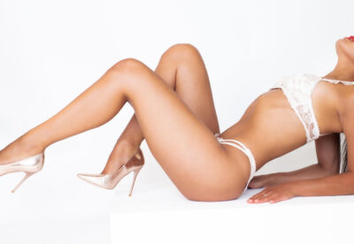 Eve leaning back on forearms, head titled back, knees bent up, one further bent than the other. Eve wears white lingerie with gold stilettos and has long black hair. NZ Pleasures.