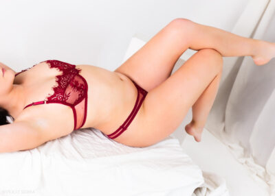 Imogen lying back, back arched, arms above head, knees bent up, calf resting on knee of opposite leg. Imogen wears deep red lingerie and has medium length black hair. NZ Pleasures.