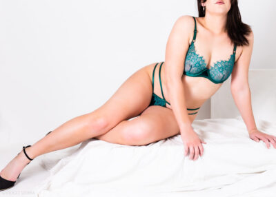 Imogen reclining with legs extended to one side, one knee bent, lifting up on hands that are to one side. Imogen wears emerald green lingerie with black heels and has long black hair. NZ Pleasures.