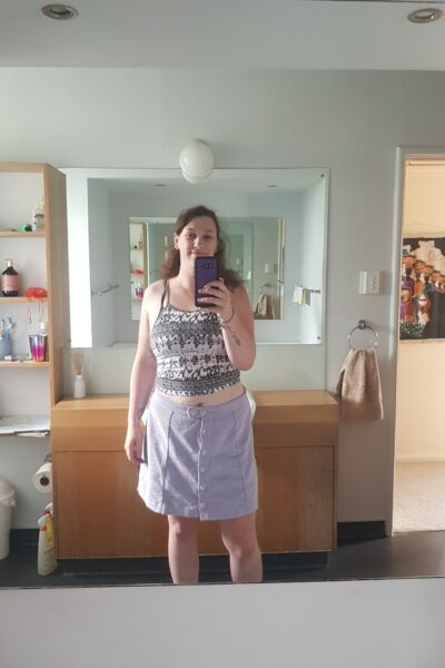 Lucy taking a selfie in the bathroom mirror. Lucy wears a grey and white singlet with a light blue skirt and has long brown hair. NZ Pleasures.